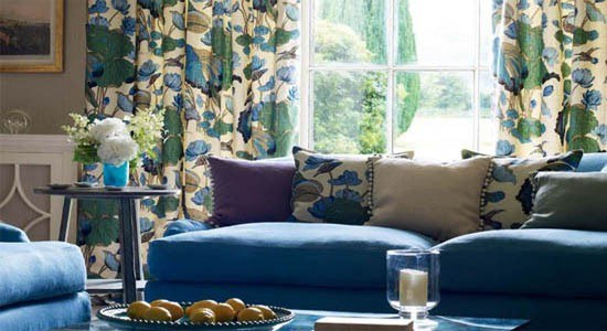 G P & J Baker fabric blue sofa with floral throw pillows and peacock print drapes