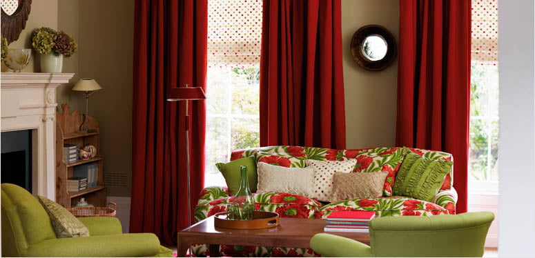 Baker Lifestyle Fabric red drapes, green floral couch with green accent chairs