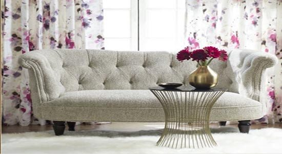 A couch and drapes upholstered using Vervain fabrics.