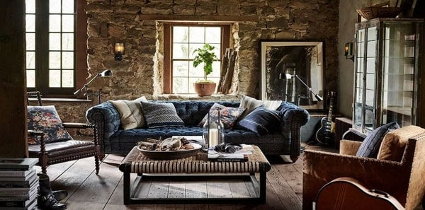Ralph Lauren home decor in a modern country setting with a blue sofa and stone walls