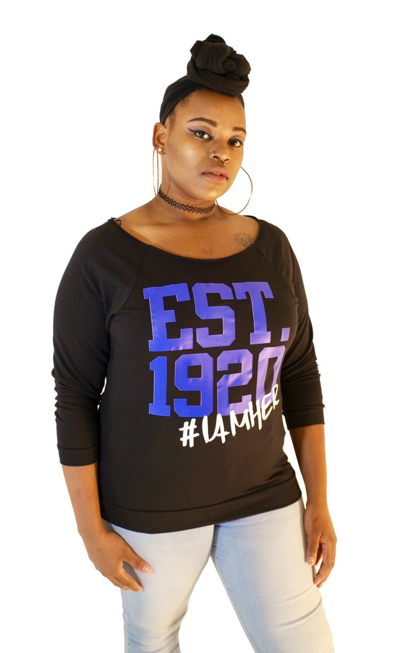 Black female wearing Black Women's Wideneck Off Shoulder with 3/4 sleeve for women with saying, EST. 1920 #IAMHER designed for the sisters of Zeta Phi Beta.