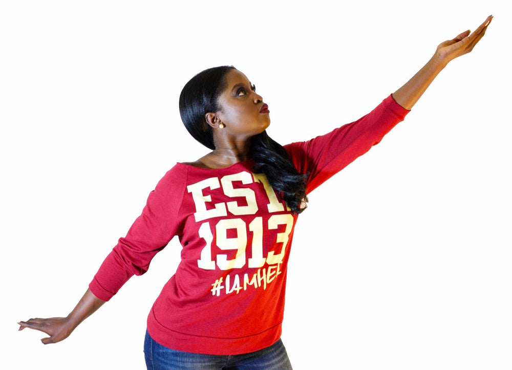 Black female wearing Scarlet Women's Wideneck Off Shoulder with 3/4 sleeve for women with saying, EST. 1913 #IAMHER designed for the sisters of Delta Sigma Theta.