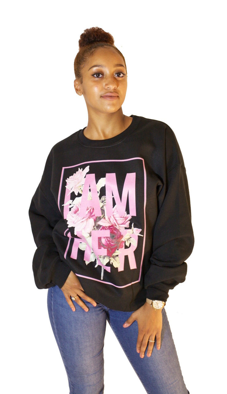 Female wearing black Women's Crewneck Sweatshirt with saying, I AM HER with Rose design in pink. For the woman who unapologetically dares to be fearless with style and grace!