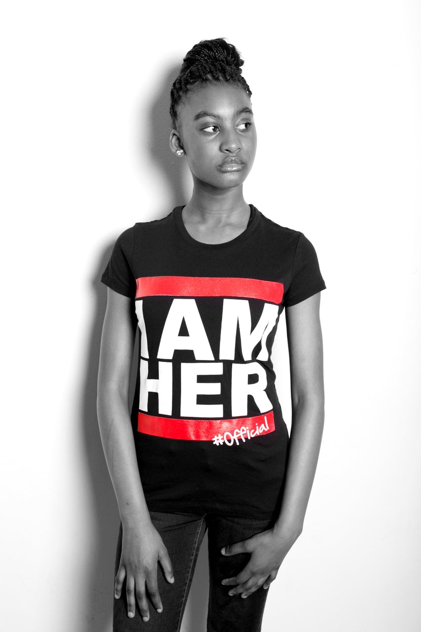 Teenage girl wearing black Graphic Tee for junior girls with saying, I AM HER. Teen fashion designed for girls who unapologetically show up in the world as she is with fashion.