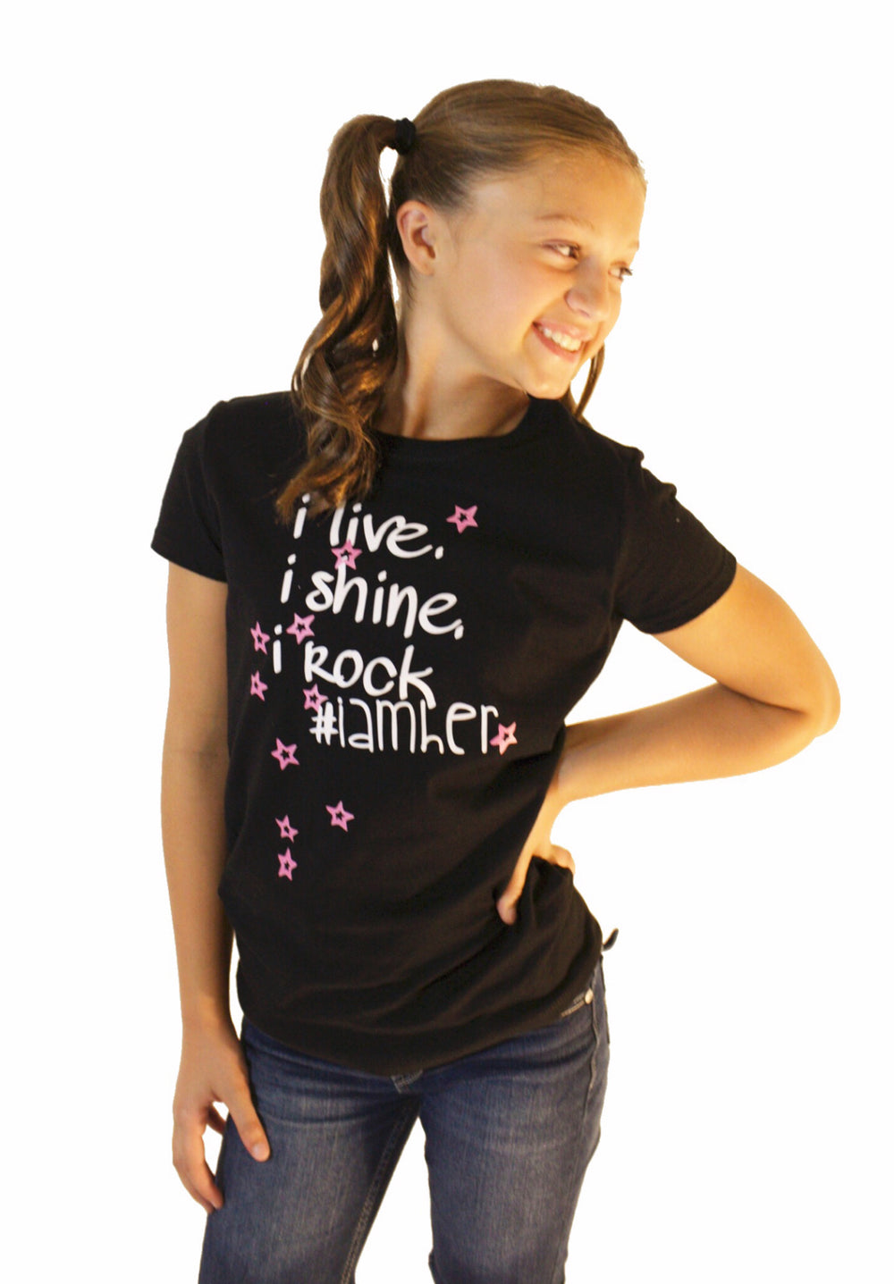 Girl wearing black graphic tee for girls with saying, I Live. I Rock. I Shine #IAMHER. Girls tees designed for her because it is never too early or too late for her to know her value and worth.