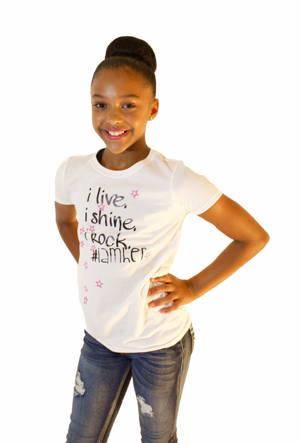 Girl wearing white graphic tee for girls with saying, I Live. I Rock. I Shine #IAMHER. Girls tees designed for her because it is never too early or too late for her to know her value and worth.