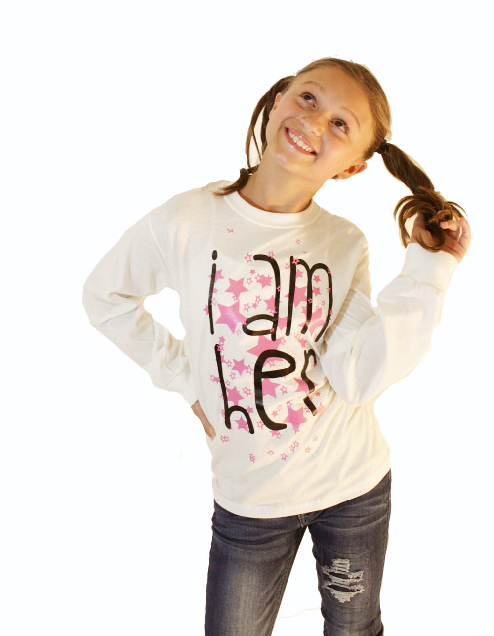 Girl wearing white longsleeve shirts for kids with saying, I AM HER. Girls fashion designed for her because it is never too early or too late for her to know her value and worth