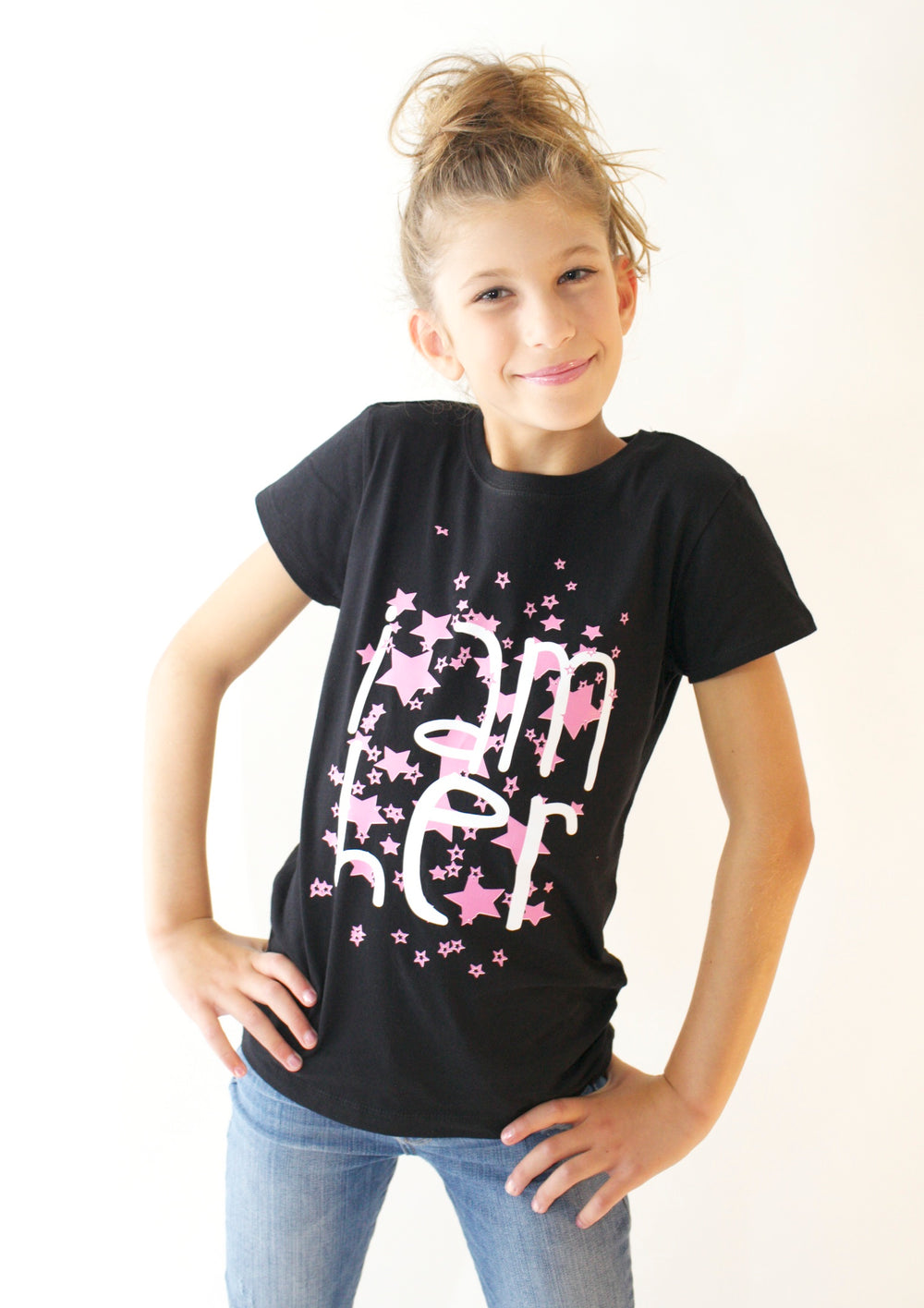 Girl wearing black graphic tee for girls with saying, I AM HER. Girls tees designed for her because it is never too early or too late for her to know her value and worth.