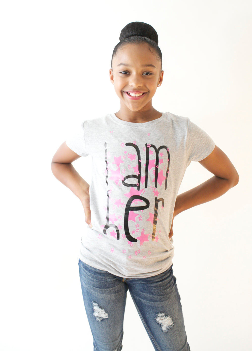Girl wearing gray graphic tee for girls with saying, I AM HER. Girls tees designed for her because it is never too early or too late for her to know her value and worth