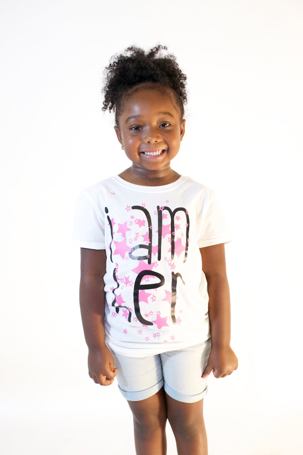 Girl wearing white graphic tee for girls with saying, I AM HER. Girls tees designed for her because it is never too early or too late for her to know her value and worth I