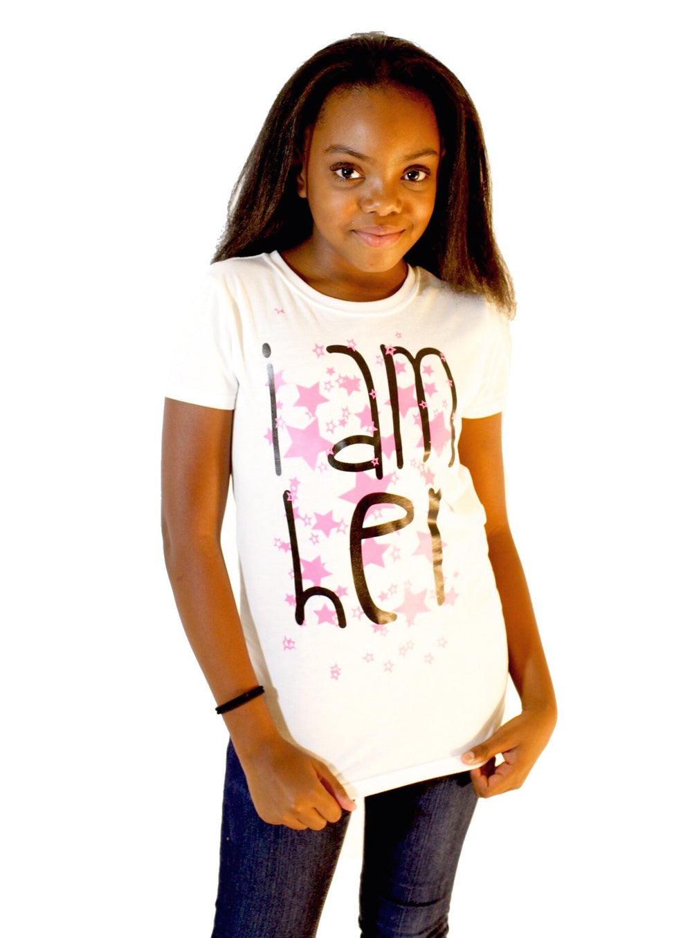Girl wearing white graphic tee for girls with saying, I AM HER. Girls tees designed for her because it is never too early or too late for her to know her value and worth.
