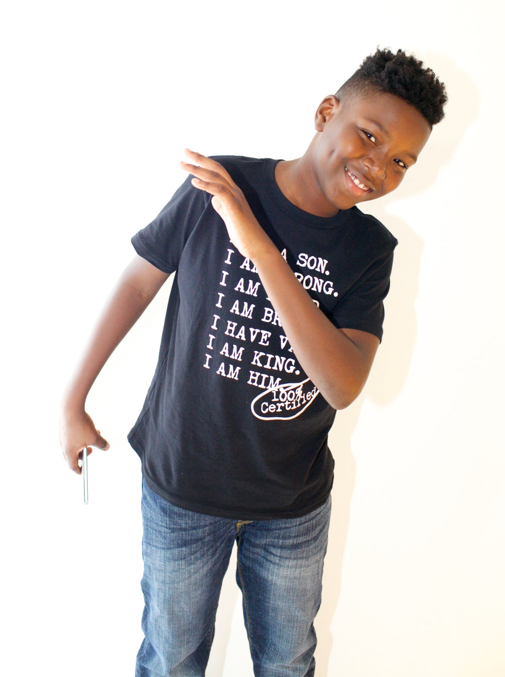 Boy wearing black graphic tee for boys with saying, I AM A SON. I AM STRONG. I AM LOVED. I AM STRONG. I AM BRAVE. I AM VALUED. I AM KING. I AM HIM -­‐ 100% CERTIFIED. Boys clothing for him because it is never too early or too late for him to know his value and worth.