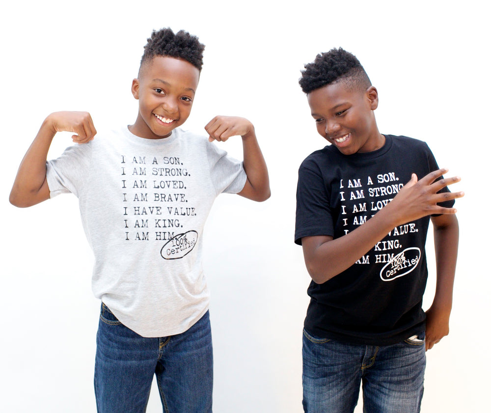 Two boys wearing black and gray graphic tees for boys with saying, I AM A SON. I AM STRONG. I AM LOVED. I AM STRONG. I AM BRAVE. I AM VALUED. I AM KING. I AM HIM -­‐ 100% CERTIFIED. Boys clothing for him because it is never too early or too late for him to know his value and worth.
