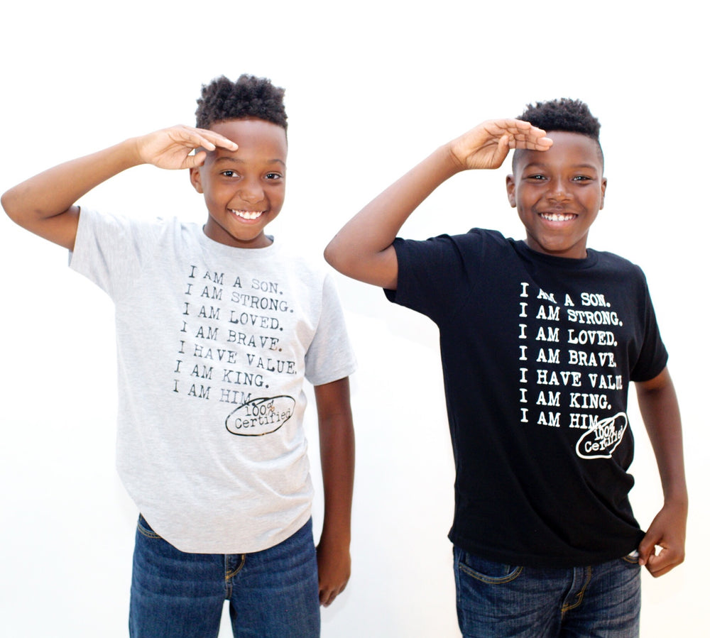 Two boy wearing black  and gray graphic tees for boys with saying, I AM A SON. I AM STRONG. I AM LOVED. I AM STRONG. I AM BRAVE. I AM VALUED. I AM KING. I AM HIM -­‐ 100% CERTIFIED. Boys clothing for him because it is never too early or too late for him to know his value and worth.