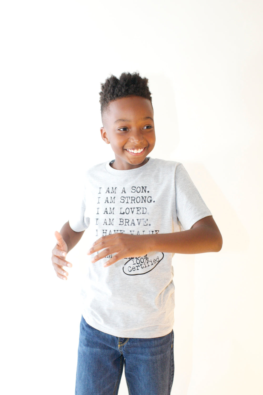 Boy wearing gray graphic tee for boys with saying, I AM A SON. I AM STRONG. I AM LOVED. I AM STRONG. I AM BRAVE. I AM VALUED. I AM KING. I AM HIM -­‐ 100% CERTIFIED. Boys clothing for him because it is never too early or too late for him to know his value and worth.