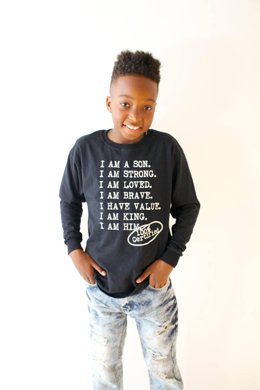 Boy wearing black Longsleeve for boys with saying, I AM A SON. I AM STRONG. I AM LOVED. I AM STRONG. I AM BRAVE. I AM VALUED. I AM KING. I AM HIM -­‐ 100% CERTIFIED. Boys clothing for him because it is never too early or too late for him to know his value and worth.