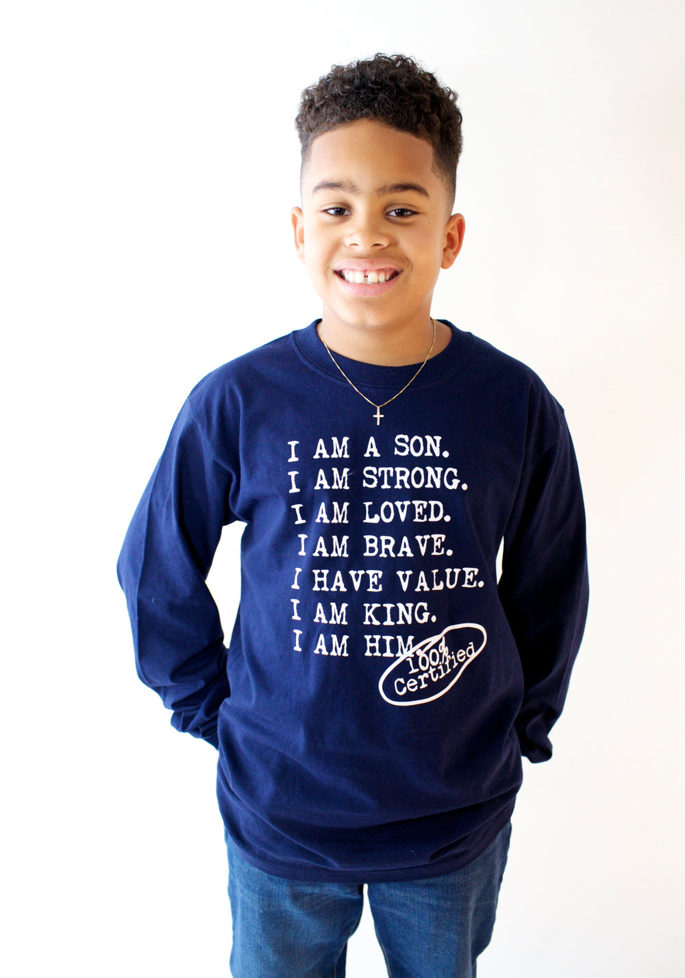 Boy wearing navy Longsleeve for boys with saying, I AM A SON. I AM STRONG. I AM LOVED. I AM STRONG. I AM BRAVE. I AM VALUED. I AM KING. I AM HIM -­‐ 100% CERTIFIED. Boys clothing for him because it is never too early or too late for him to know his value and worth.