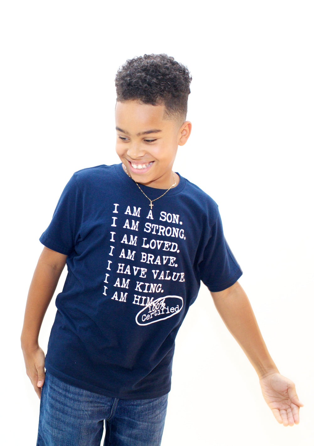 Boy wearing navy graphic tee for boys with saying, I AM A SON. I AM STRONG. I AM LOVED. I AM STRONG. I AM BRAVE. I AM VALUED. I AM KING. I AM HIM -­‐ 100% CERTIFIED. Boys clothing for him because it is never too early or too late for him to know his value and worth.