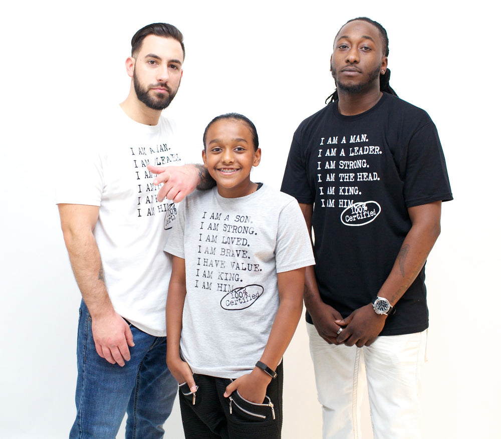 Three males wearing graphic tees for boys with saying, I AM A SON. I AM STRONG. I AM LOVED. I AM STRONG. I AM BRAVE. I AM VALUED. I AM KING. I AM HIM -­‐ 100% CERTIFIED. Boys clothing for him because it is never too early or too late for him to know his value and worth.