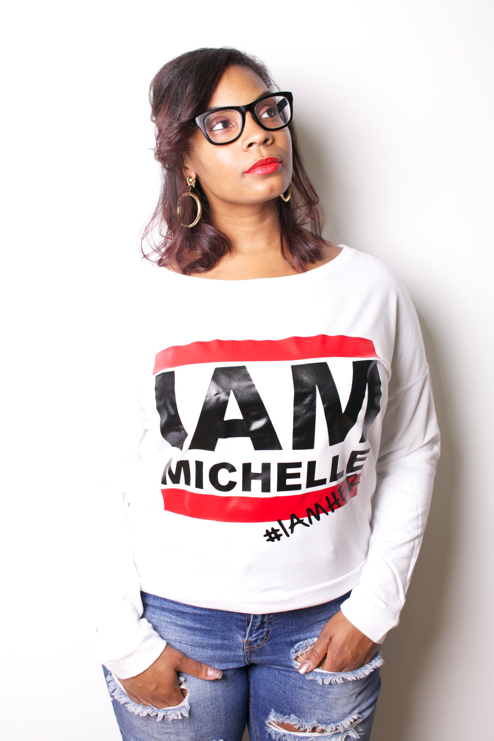 Female wearing white Women's Longsleeve Tee with saying, I AM Michelle. I AM MICHELLE Women's Long Sleeve Tee is for the girl who sees herself when she sees Former First Lady Michelle Obama.