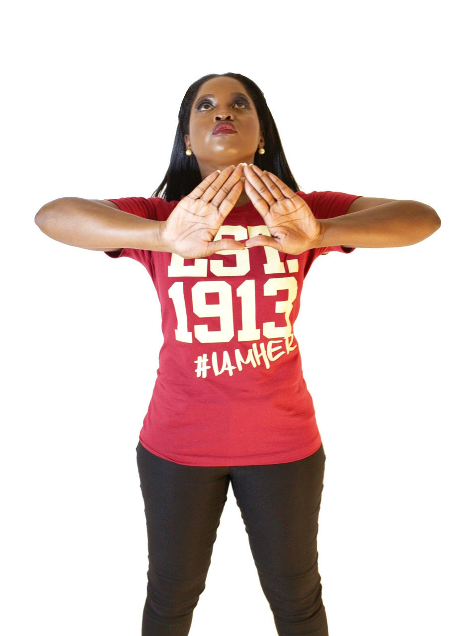 Black female wearing Scarlet Graphic Tee for women with saying, EST. 1913 #IAMHER designed for sisters of Delta Sigma Theta.