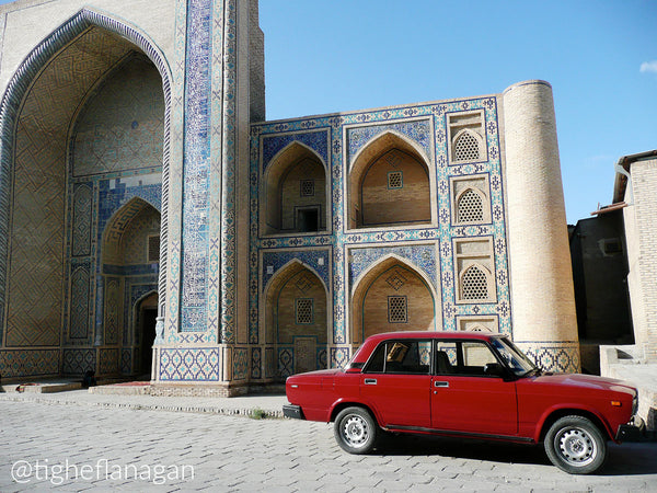Red Lada parked in front of historic building in Bukhara, Uzbekistan.