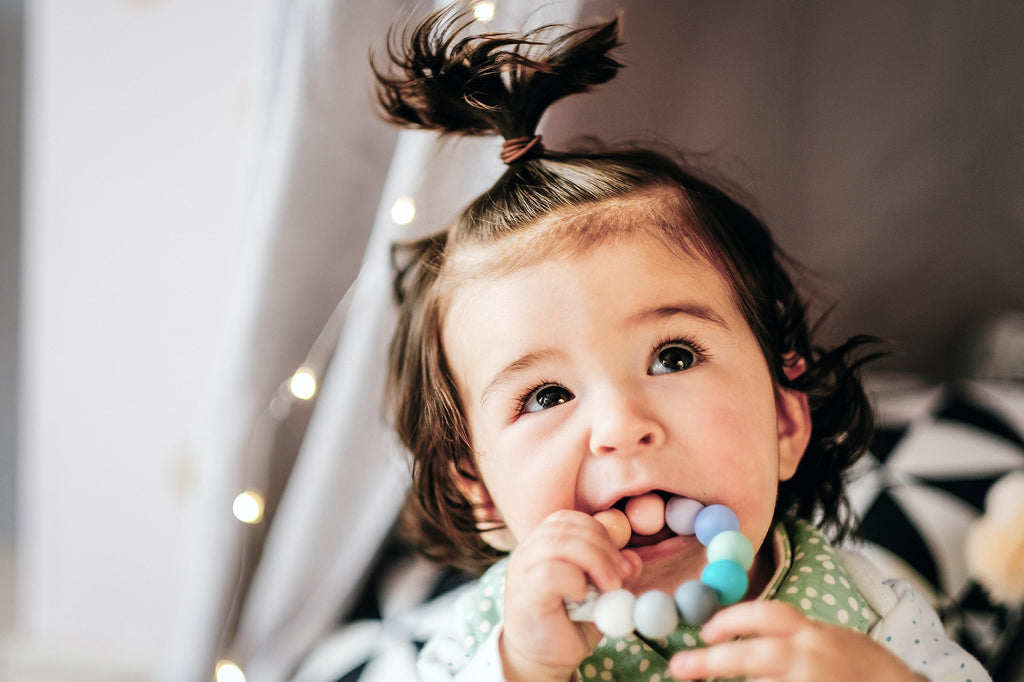 Baby with Rainbow Coloured teething toy in mouth