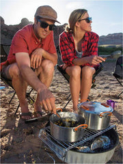 2 campers cooking wearing Flyshacker flannel shirt