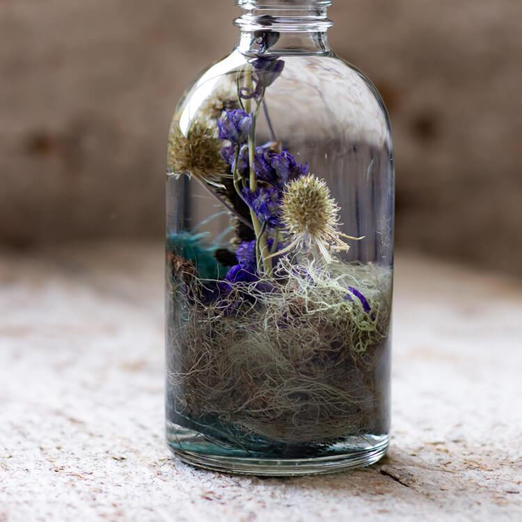 Zoom shot of a dreamy blue botanical bottle, Reverie number 12. The collection will inspire your artistic soul to be imaginative and create your own fantasy.