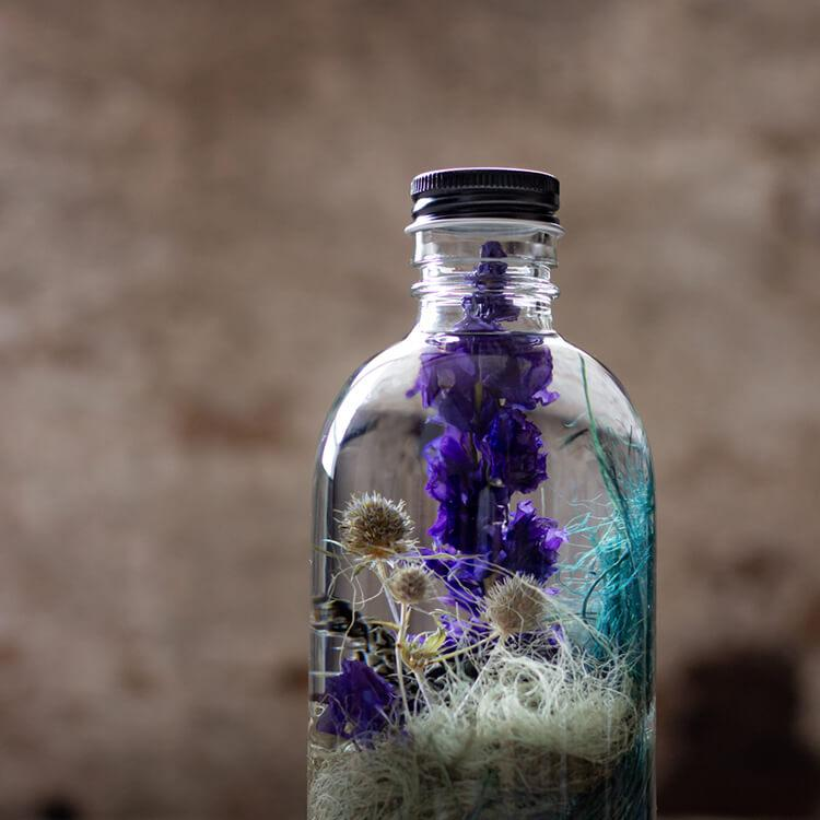 Zoom shot of a dreamy blue botanical bottle, Reverie number 13. The collection will inspire your artistic soul to be imaginative and create your own fantasy.