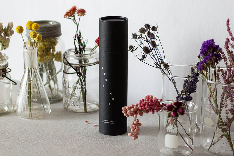An elegant, black, gift-ready tube packaging shown with the selection of dried flowers for DEAR ONE collection