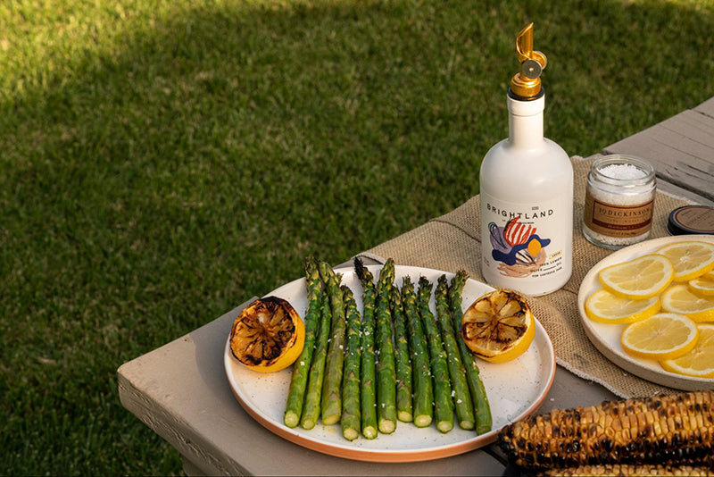 a bottle of oil on a table with grilled vegetables