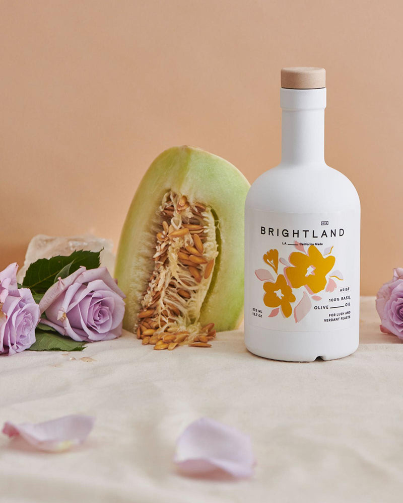 a bottle of brightland oil next to a melon