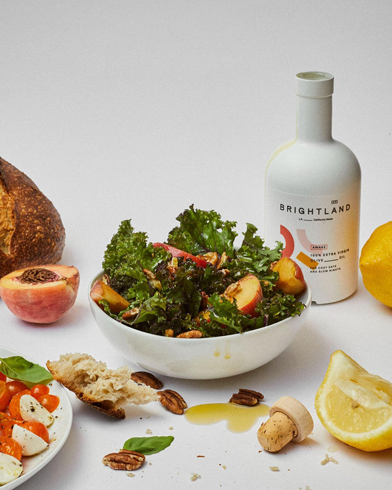 a bottle of brightland oil with a salad and fresh fruit