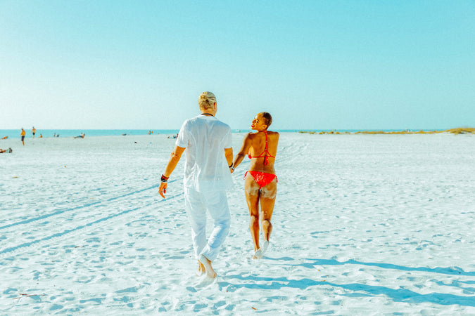 interracial couple running together on the beach in Sarasota Florida female wearing pink bikini male wearing white shirt and pants
