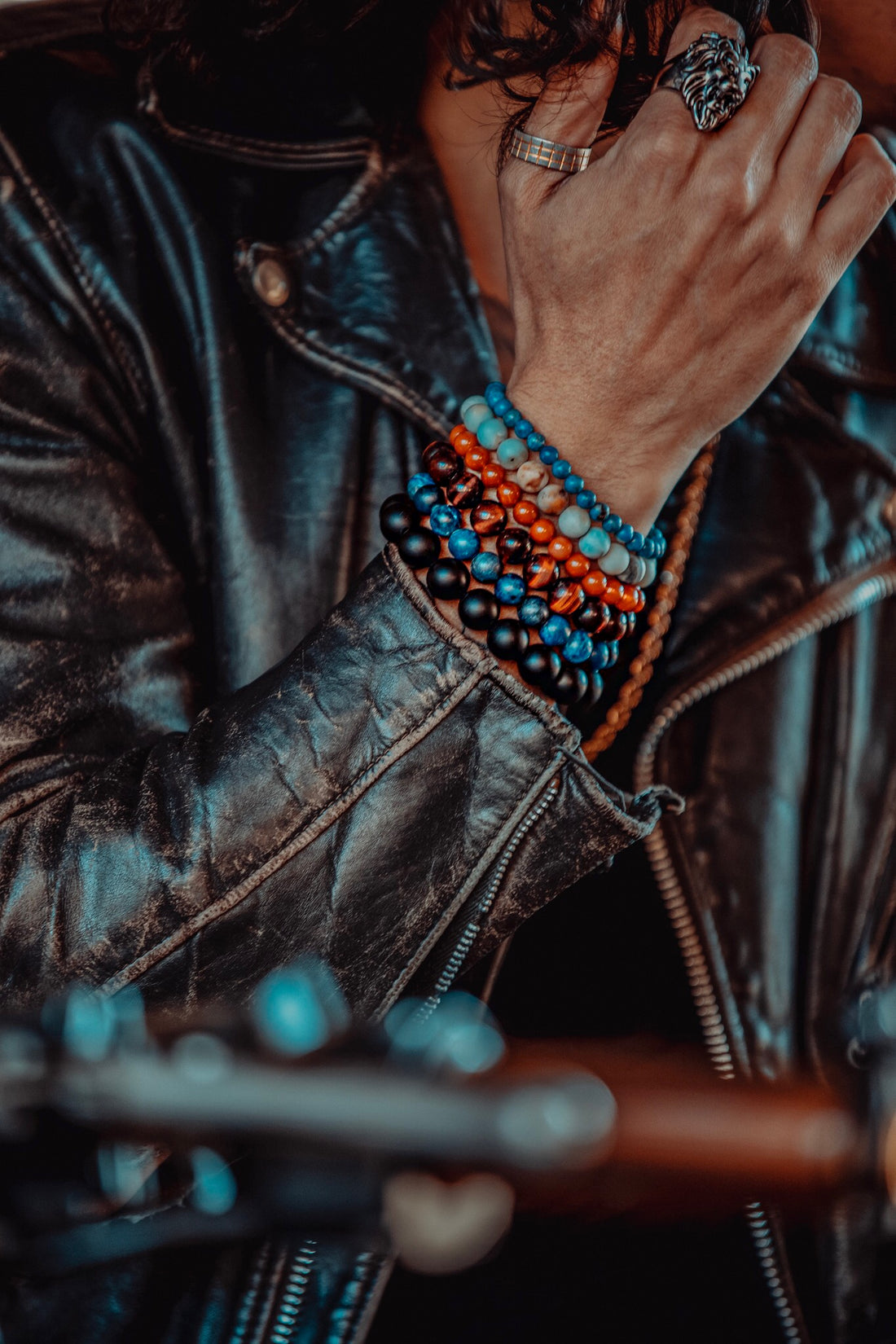 "<img alt=""male model wearing brown leather jacket and natural stone bracelets sitting on a motorcycle outside in Manhattan NY"