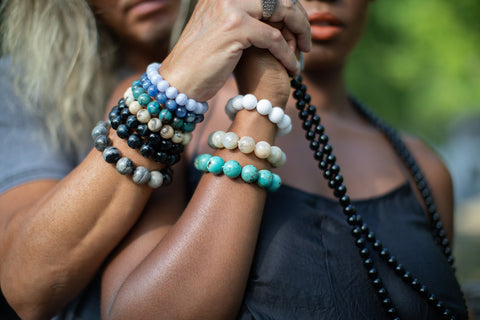 Man and Woman wearing gemstone bracelets.