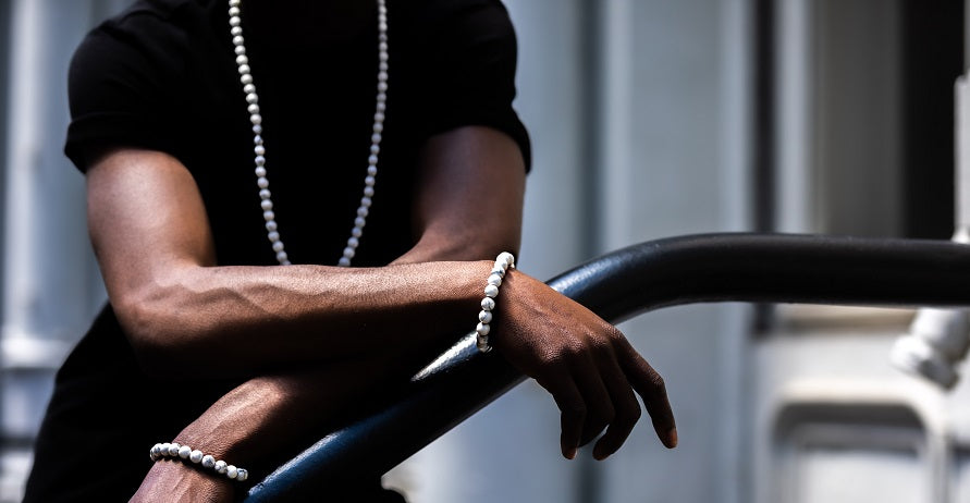 "<img src=""IMG_8978.JPG"" alt=""African American male model leaning on stair railing wearing a black t shirt with a Howlite Natural Stone Necklace and two Howlite Natural Stone Bracelets"">"
