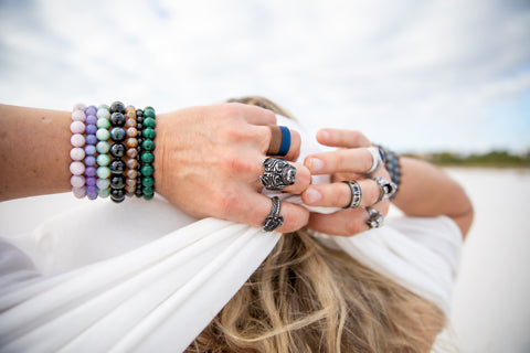Man with hands behind his head wearing gemstone bracelets