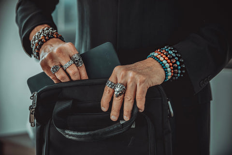 Man holding computer bag wearing silver rings and gemstone bracelets.