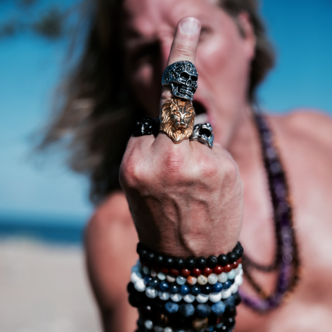 Male giving the middle finger wearing rings and bracelets