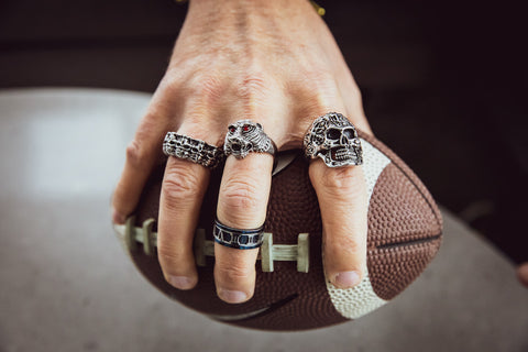 Man holding football wearing rings.