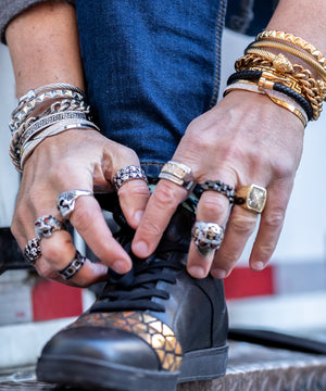 Caucasian model wearing a variety of stainless steel bracelets and rings designed by PlayHardLookDope bending over lacing his shoe outside against a delivery truck in chinatown manhattan