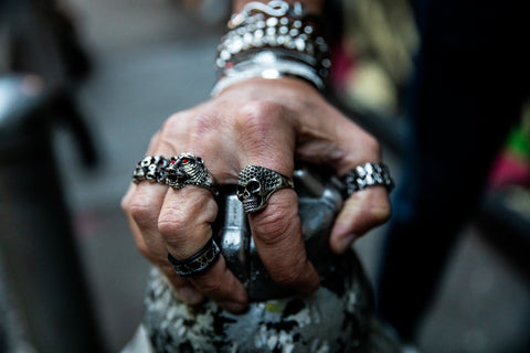 Caucasian model wearing silver skull head and lion head silver 316L high- grade stainless steel rings holding a fountain stand outside in chinatown manhattan rings handmade and designed by playhardlookdope