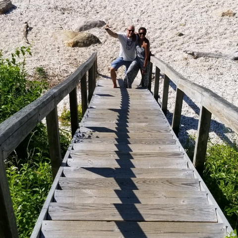 Couple standing at the bottom of a staircase on the beach
