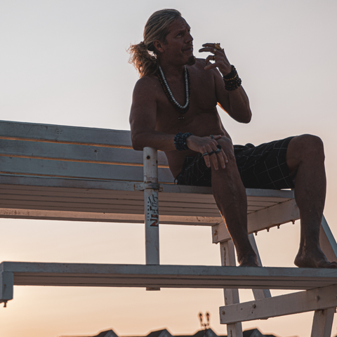 male sitting in lifeguard chair enjoying sunset