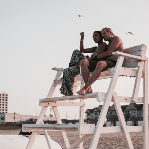 couple sitting in lifeguard chair enjoying sunset