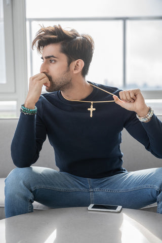indian male model sitting on couch while modeling a gold stainless steel cross necklace and an assortment of men's natural stone bracelets