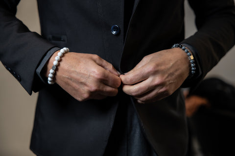 Man wearing a suit and two gemstone bracelets.