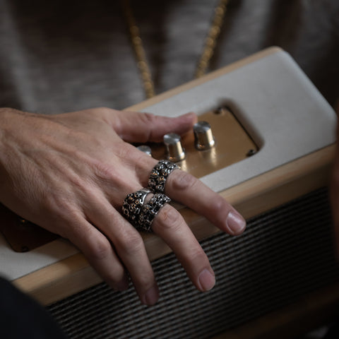 Man holding music speaker wearing men's rings.
